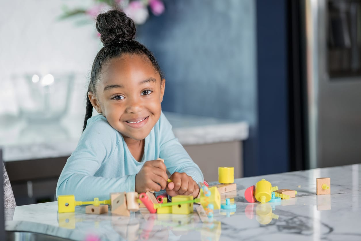 Adorable African American elementary age little girl is using a STEM educational toy at home in modern kitchen. She is looking at the camera and smiling.