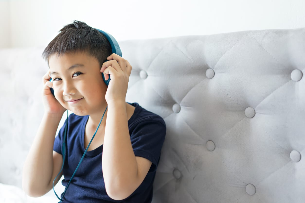 Happy Little boy listening to music on bed at bedroom for relax
